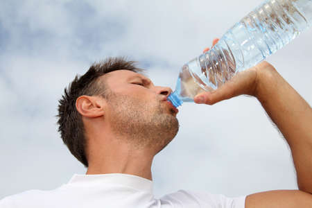 Gros plan de l'homme de l'eau potable de la bouteille Banque d'images