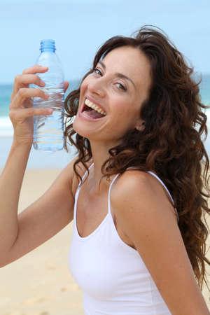woman 40 years: Beautiful woman drinking water at the beach  Stock Photo