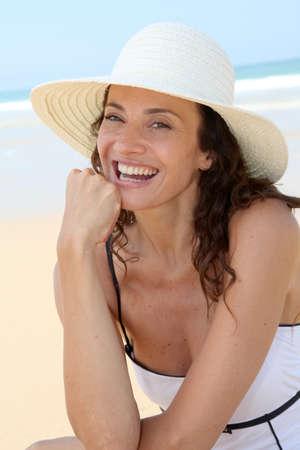 Mooie vrouw zittend op het strand met stro hoed