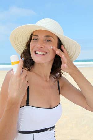 sun shade: Beautiful woman at the beach putting sunscreen on her body