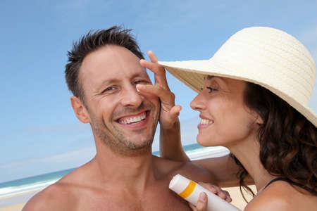 Woman putting sunblock on her boyfriends nose photo