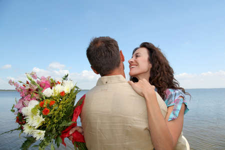 surprising: Man surprising woman with bunch of flowers Stock Photo