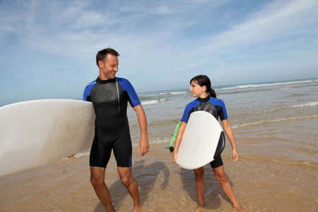 Father and daughter surfing in the ocean photo