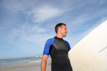 40 years old man: Man holding surfboard at the beach