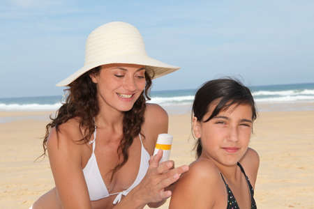 Mother spreading sunscreen on her daughters shoulders photo