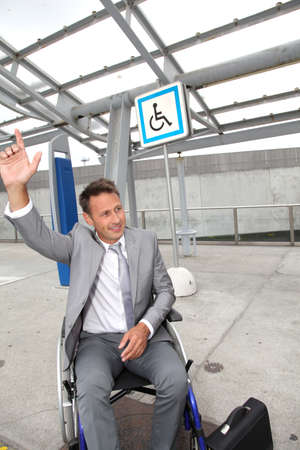 Businessman in wheelchair calling out for a taxi photo