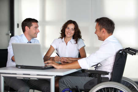 disable: Businessman in wheelchair working in the office with colleagues