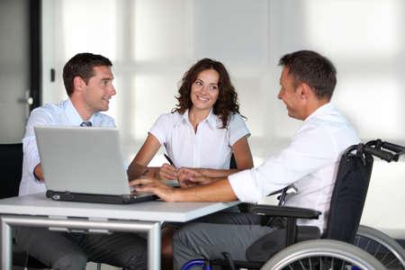 handicap: Imprenditore in sedia a rotelle con i colleghi di lavoro in ufficio  Archivio Fotografico