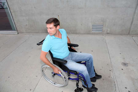 Young man using wheelchair in town Stock Photo - 7698641
