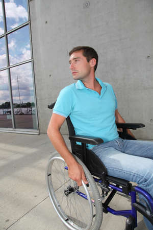 Young man using wheelchair in town photo
