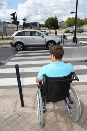 handicap: Young man using wheelchair in town