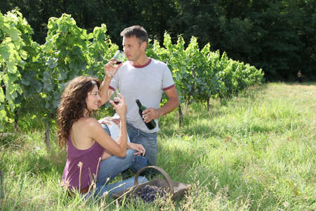 40 year old woman: Happy vinegrowers testing wine in vineyard