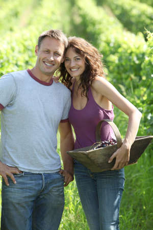 40 year old: Happy couple standing in vineyard