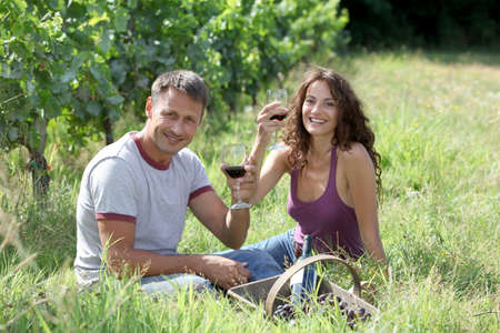 40 year old: Couple of winegrowers drinking wine in vineyard Stock Photo