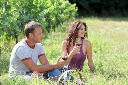 wine testing: Couple of winegrowers drinking wine in vineyard Stock Photo