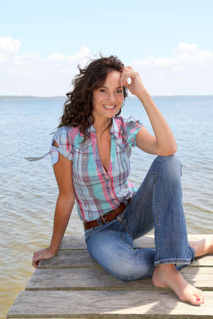 woman 40 years: Woman sitting on a pontoon by a lake in summer