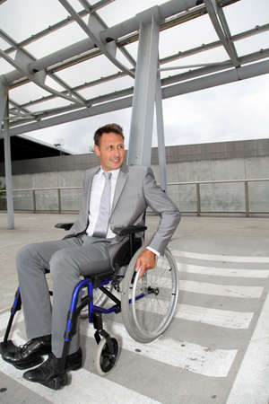 Businessman in wheelchair waiting for a taxi photo