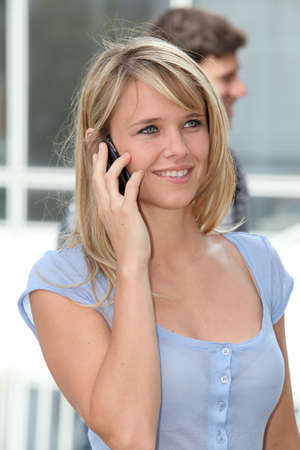 phonecall: Closeup of young woman with mobile phone at college campus