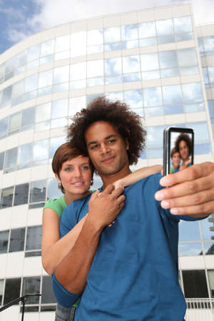 Young couple taking picture of itself with mobile phone photo