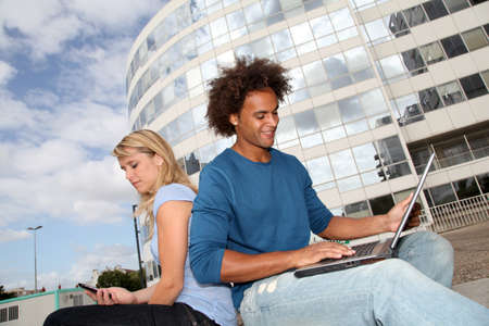 Couple of students working on laptop computer photo