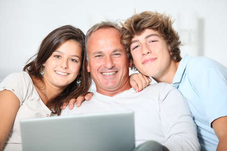 group of teens: Family at home with laptop computer