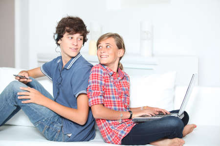 sister: Teenagers with music player and computer at home Stock Photo