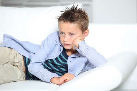 Young boy laying on a sofa at home photo