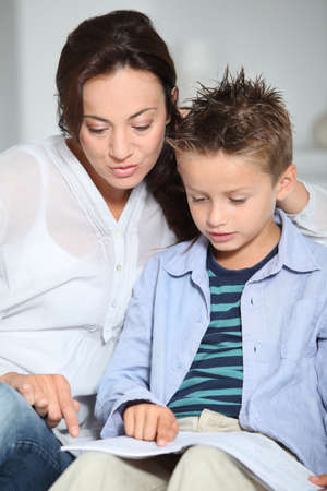 blonde mom: Littme boy and mother sitting on sofa at home with book