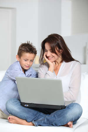 Little boy and mother sitting on sofa at home with laptop photo