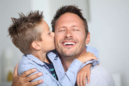Little bond boy giving a kiss to his dad photo