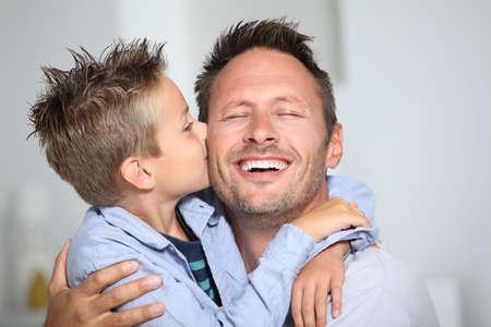 padres: Ni�o peque�o de enlace dando un beso a su padre  Foto de archivo
