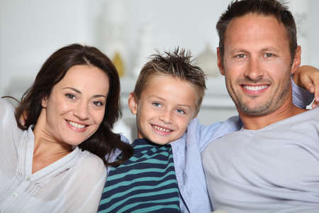 Closeup of parents and child relaxing at home on sofa photo