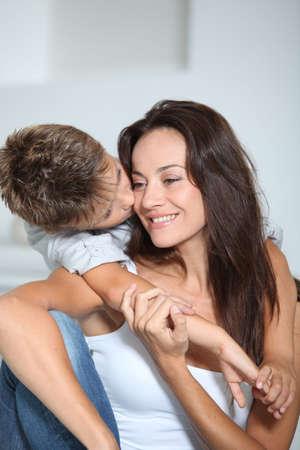 Little boy kissing her mom  photo