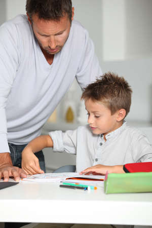 Father helping son to do homework photo