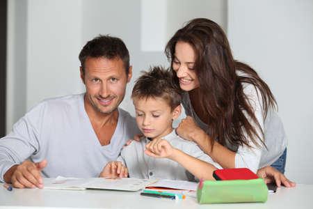 deberes: Padres ayudando a hijo a que hagan sus deberes  Foto de archivo