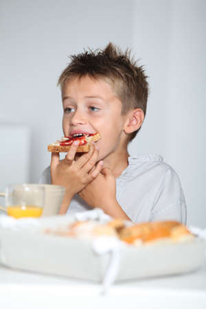 Little blond boy eating slice of bread photo