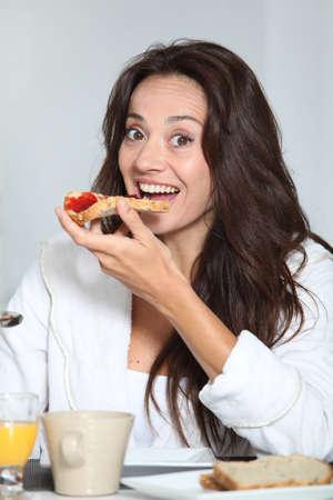 Beautiful woman having breakfast at home photo