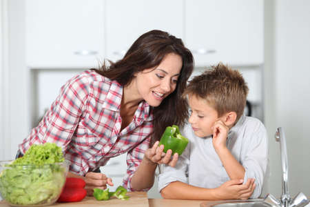 Mother cooking with son in kitchen photo
