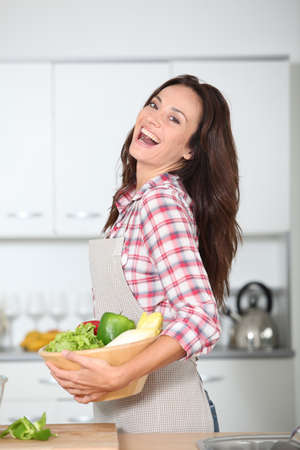 Beautiful woman stading in kitchen with apron