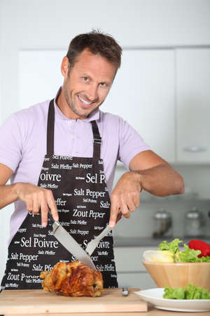 Man in kitchen with apron cooking chicken photo
