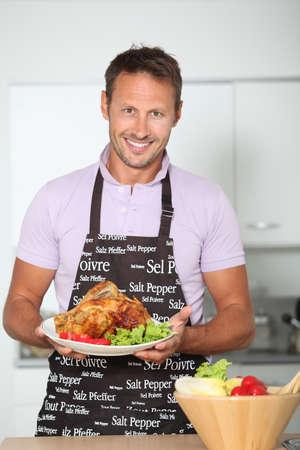 jasschort: Man in keuken met schort koken kip Stockfoto