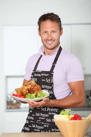 aprons: Man in kitchen with apron cooking chicken Stock Photo