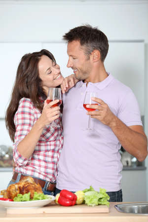 Couple drinking wine while fixing dinner photo