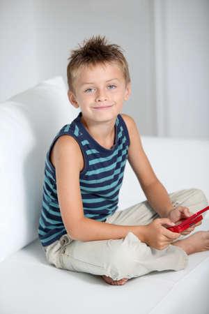 jugando videojuegos: Ni�o jugando videojuegos en sof�