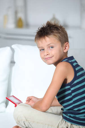 Little boy playing video games on sofa photo