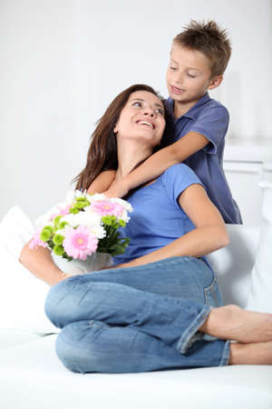 Little boy giving flowers to his mom on mothers day photo