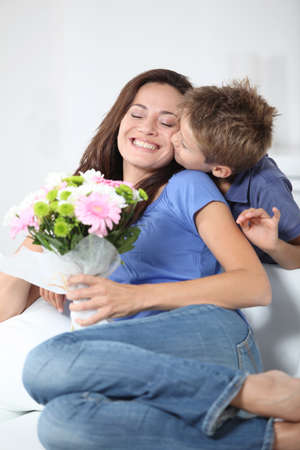 Little boy kissing his mom on mothers day photo