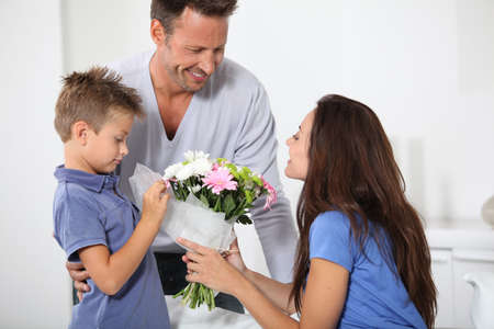 Father and child giving flower to mother photo