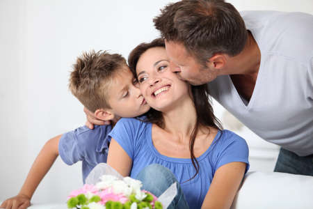 mothers: Father and chikd kissing mother for birthday