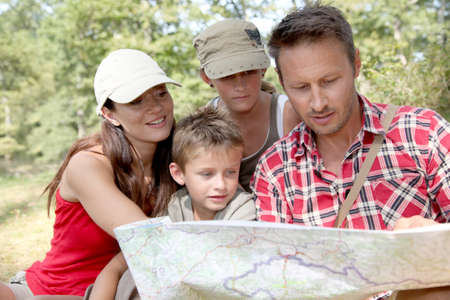 trek: Family looking at map on a hiking day